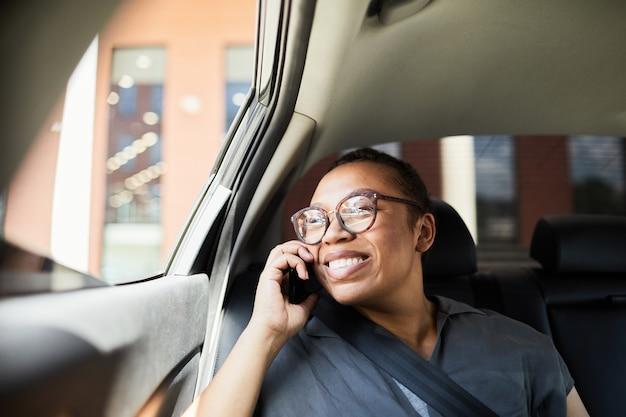 Femme heureuse africaine à lunettes parlant au téléphone portable pendant son trajet en voiture