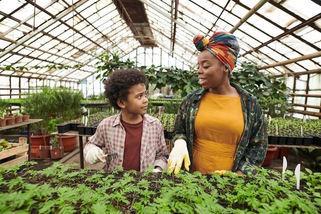 Femme heureuse africaine parlant à son enfant pendant qu'ils plantent des plantes en serre