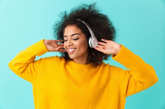 Femme heureuse afro-américaine en chemise jaune, écouter de la musique via des écouteurs sans fil avec sourire, isolé sur mur bleu