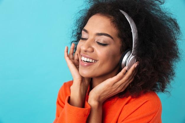 Femme heureuse afro-américaine en chemise orange, écouter de la musique via des écouteurs avec sourire, isolé sur mur bleu