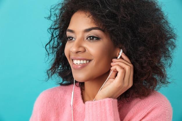 Femme heureuse afro-américaine dans des vêtements décontractés, écouter de la musique via un casque blanc avec sourire, isolé sur mur bleu