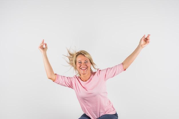 Femme heureuse âgée en chemisier rose avec les mains levées