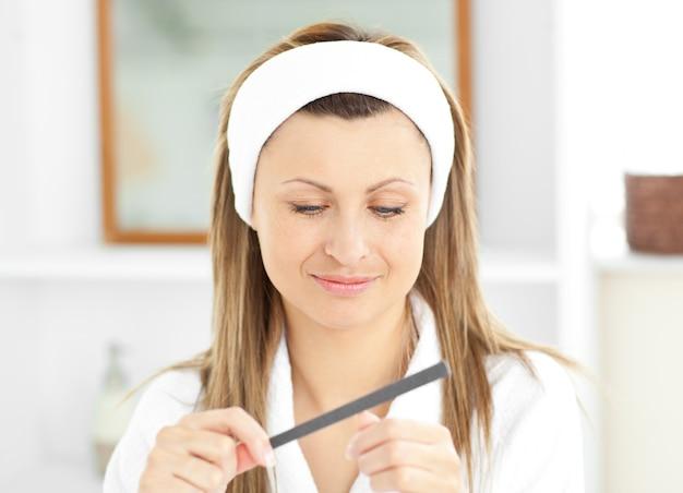 Femme heureuse à l'aide d'une lime à ongles portant une robe de bain debout dans la salle de bain