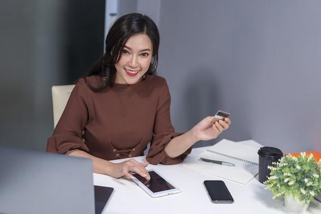 Femme heureuse à l'aide d'une tablette numérique pour faire des achats en ligne avec carte de crédit