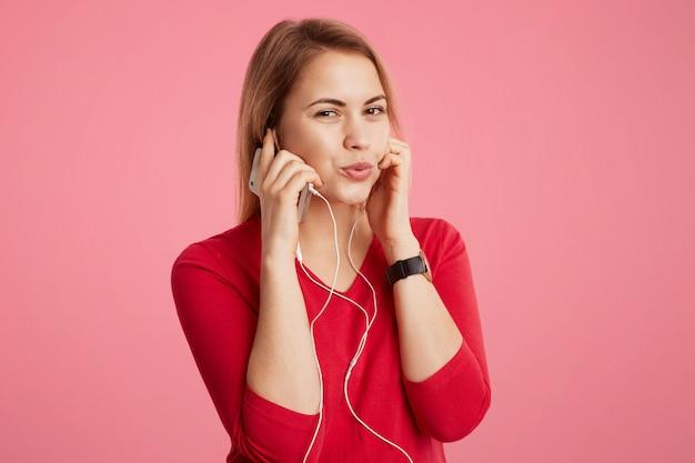 Une femme heureuse aime sa piste préférée dans les écouteurs