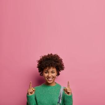 Une femme heureuse à l'air agréable invite à monter, pointe l'index vers le haut, montre où trouver les meilleures réductions, porte un pull vert, des modèles contre un mur rose, fait de la publicité pour quelque chose