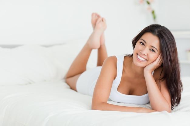 Femme heureuse allongée sur le lit avec les jambes croisées regardant dans la caméra