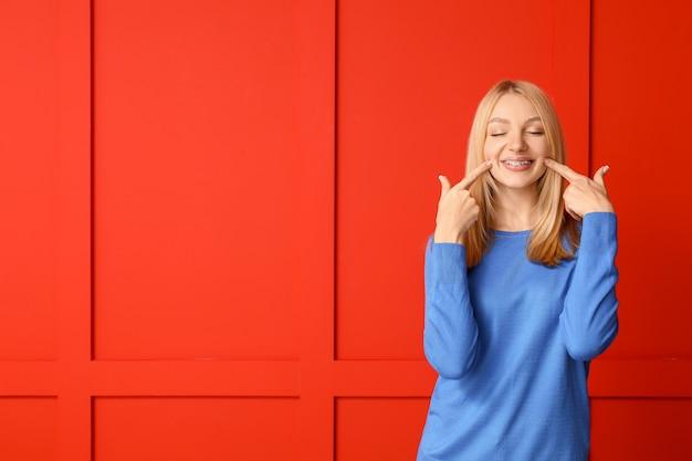 Femme heureuse avec des appareils dentaires sur la couleur