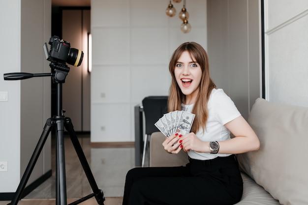 Femme heureuse avec de l'argent vidéo tutoriels d'enregistrement pour blog en ligne sur internet à la maison sur le canapé