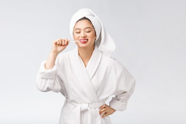 Femme heureuse asiatique avec brosse à dents dans l'humeur du matin peignoir.