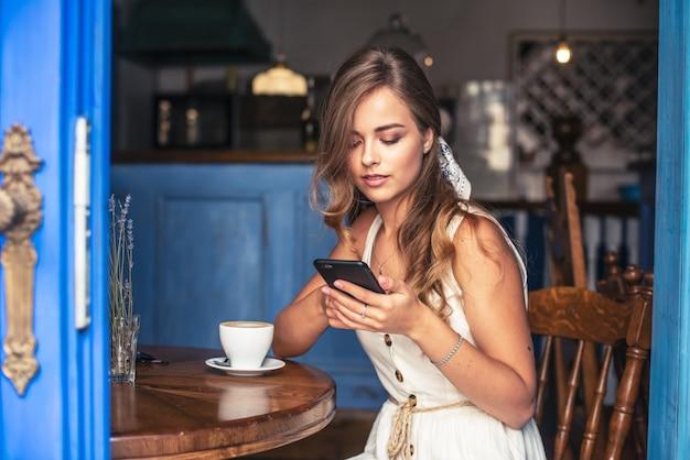 Femme heureuse, assis dans un café, parler par téléphone mobile.