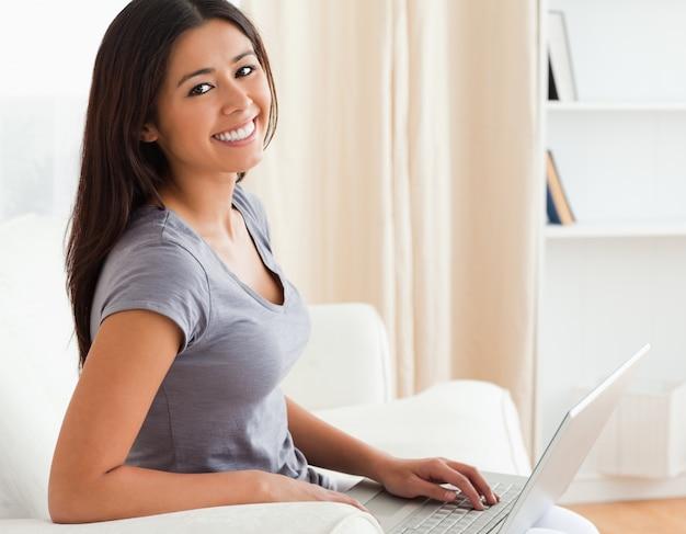 Femme heureuse assise sur le canapé avec ordinateur portable regardant dans la caméra