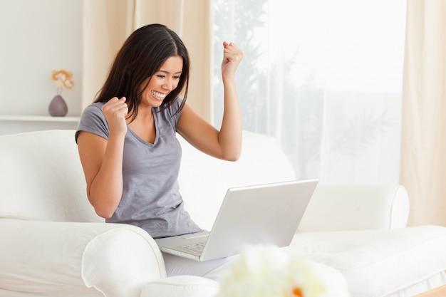 Femme heureuse assise sur le canapé avec ordinateur portable