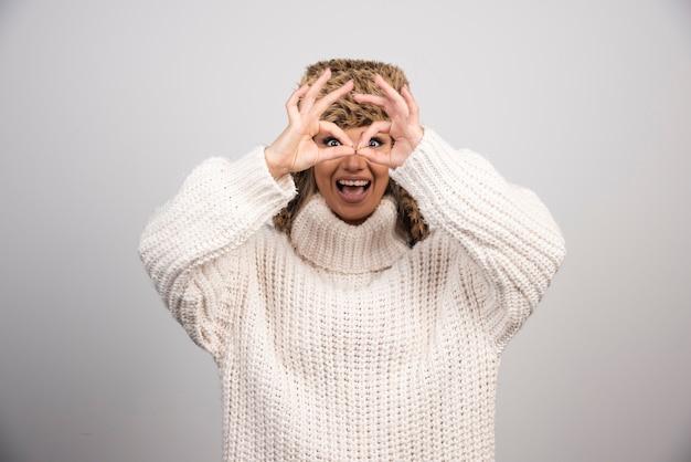 Une femme heureuse au beau chapeau faisant un geste ok comme des jumelles.