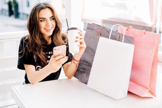 Femme heureuse au café après le shopping