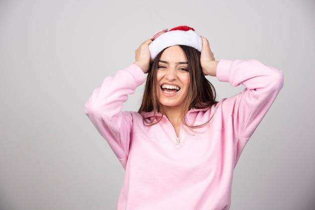 Une femme heureuse au chapeau rouge du père noël posant.