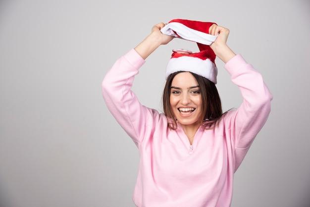 Une femme heureuse au chapeau rouge du père noël tenant un chapeau au-dessus.
