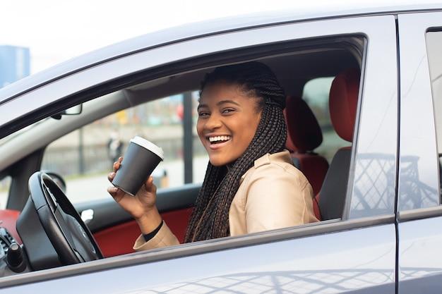 Femme heureuse au volant d'une voiture, boire du café, afro-américain