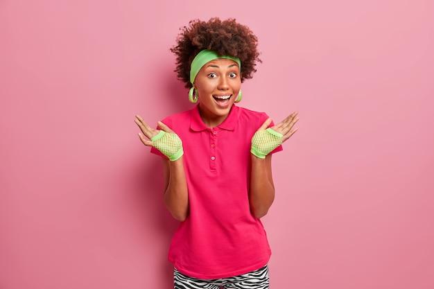 Femme heureuse aux cheveux bouclés naturels, soulève les paumes, se sent confuse, rit positivement, porte des gants de sport, t-shirt rose vif, pose à l'intérieur