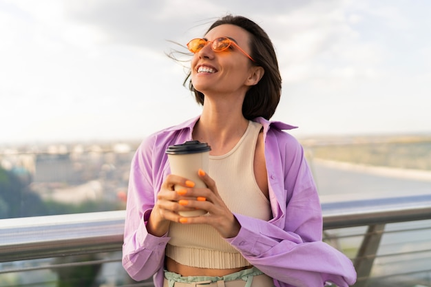 Femme heureuse aux cheveux courts en tenue d'été élégante, boire du café sur le pont moderne de thr