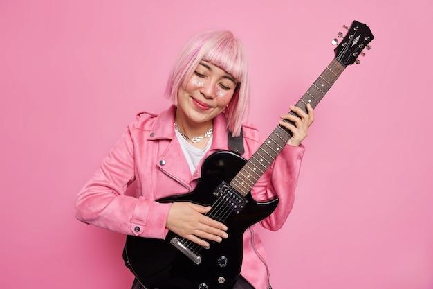 Une femme heureuse aux cheveux roses incline la tête joue de la guitare acoustique aime la mélodie préférée se prépare pour un concert de rock n roll porte des vêtements à la mode pose en studio contre un mur rose. notion musicale