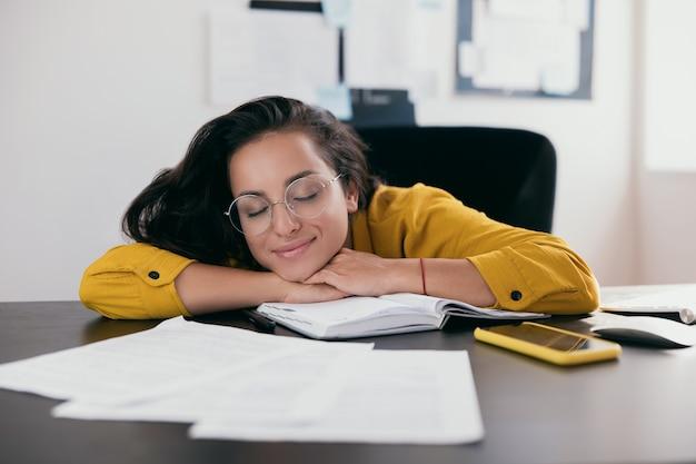 Femme heureuse aux longs cheveux bruns portant un chemisier jaune vif et des lunettes rondes prend une pause