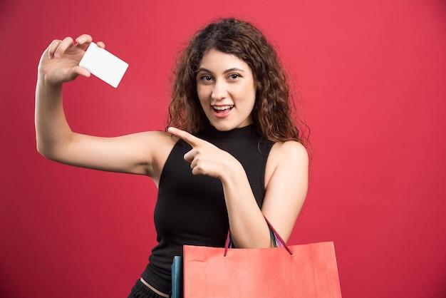 Femme heureuse avec beaucoup de sacs et carte bancaire sur rouge