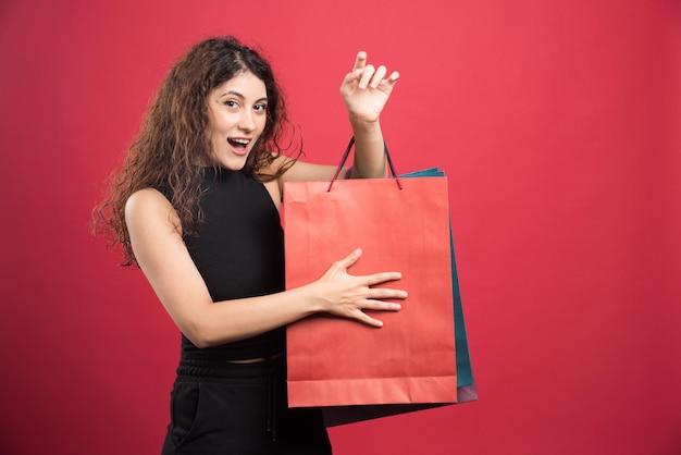 Femme heureuse avec beaucoup de sacs sur le rouge
