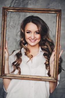 Femme heureuse avec de beaux cheveux ondulés souriant à travers le cadre.