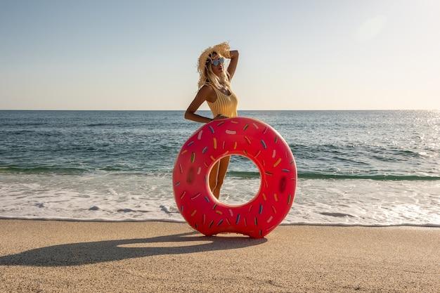 Femme heureuse avec beignet gonflable sur une plage tropicale.