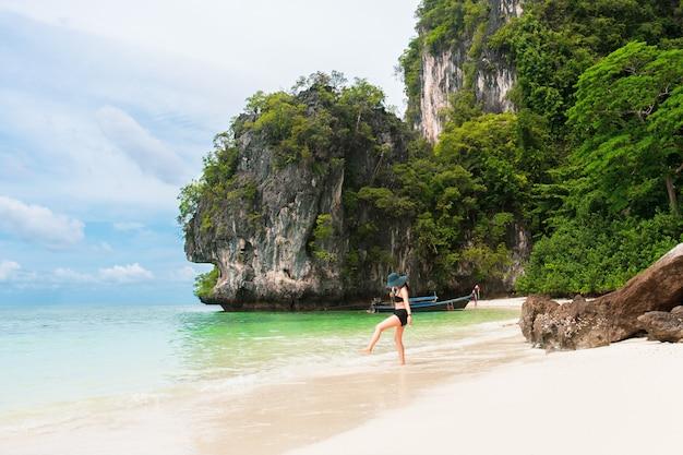 Femme heureuse en bikini et chapeau de soleil marchant sur la plage de la mer.
