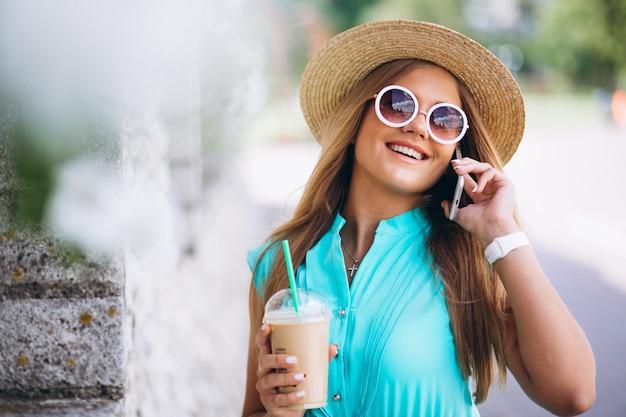 Femme heureuse, boire du café et parler au téléphone