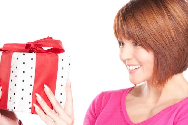 Femme heureuse avec boîte-cadeau sur mur blanc