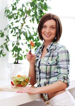 Femme heureuse avec bol de salade fraîche