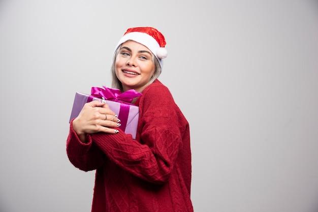 Une femme heureuse en bonnet de noel embrasse le cadeau de noël.