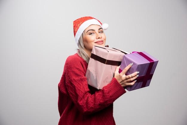 Une femme heureuse en bonnet de noel embrasse les cadeaux de noël.