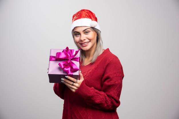 Femme heureuse en bonnet de noel offrant un cadeau de noël.