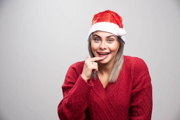 Femme heureuse en bonnet de noel posant sur fond gris.