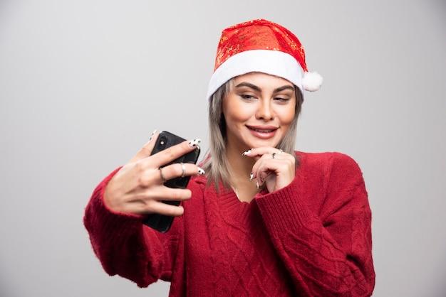 Femme heureuse en bonnet de noel prenant une photo d'elle-même.