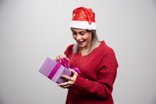 Femme heureuse en bonnet de noel regardant le cadeau de noël.