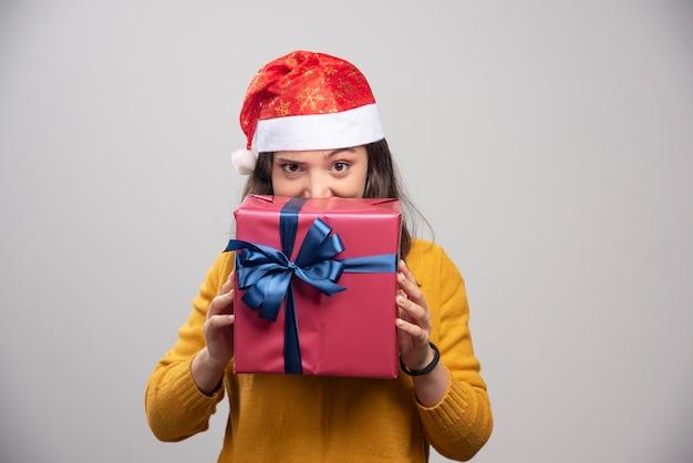 Femme heureuse en bonnet de noel se cachant derrière une boîte-cadeau.