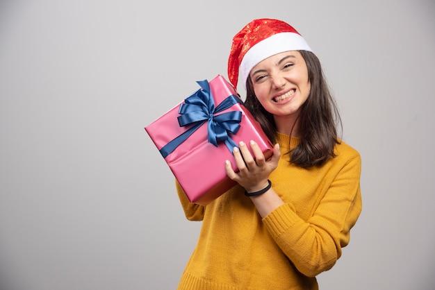 Femme heureuse en bonnet de noel tenant une boîte-cadeau.