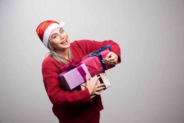 Femme heureuse en bonnet de noel tenant un tas de coffrets cadeaux.