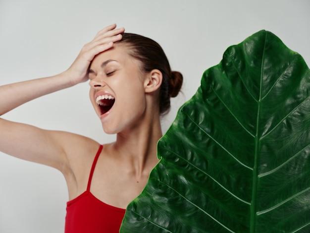 Une femme heureuse avec la bouche ouverte touche sa tête avec la main sur fond clair