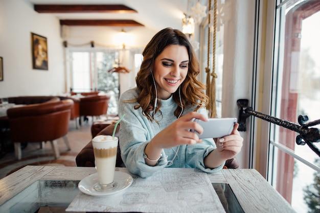 Femme heureuse avec des boucles au café en utilisant un téléphone intelligent et souriant