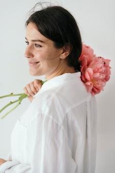 Femme heureuse avec un bouquet de pivoine coucher de soleil corail