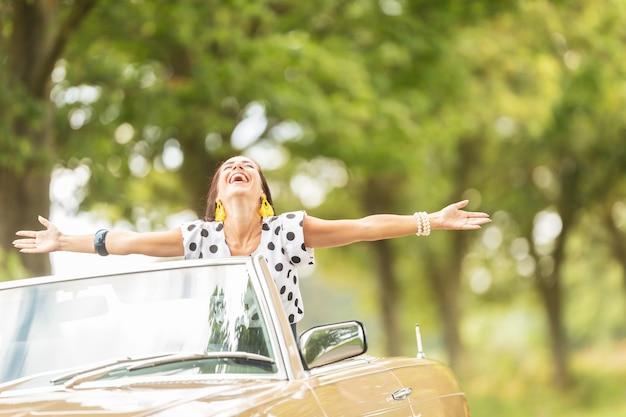Femme heureuse avec les bras grands ouverts, profitant de la liberté sur un roadtrip automobile décapotable.