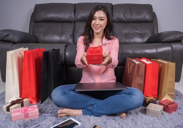 Femme heureuse avec un cadeau de noël dans le salon
