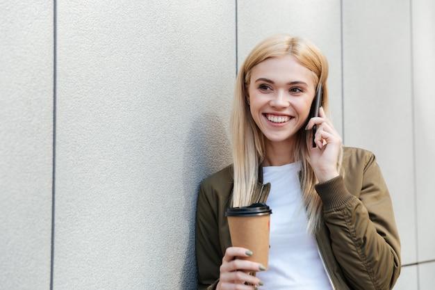 Femme heureuse avec café parler sur smartphone
