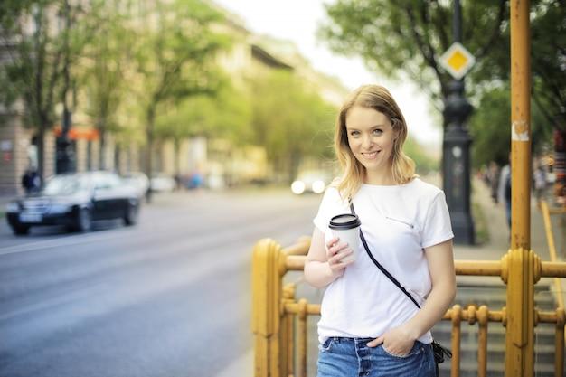 Femme heureuse avec un café pour aller
